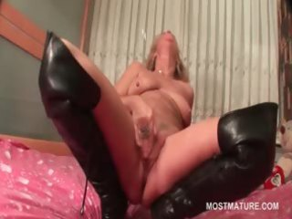 aged in leather boots doing herself in bed
